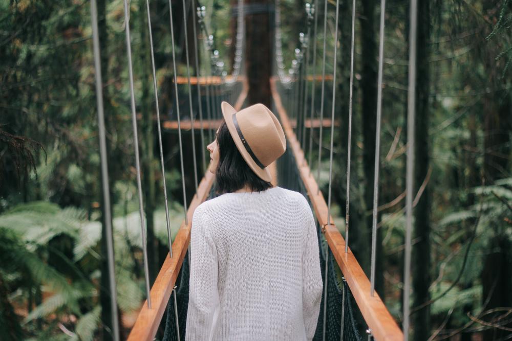 Woman Walking Across Rope Bridge