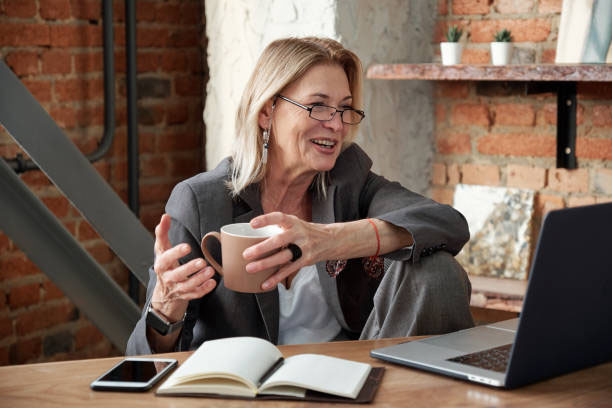 Older Woman In Suit Jacket Looking At Laptop With Coffee Cup In Hand, Talking With Someone On Screen